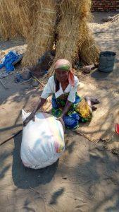Oude vrouw krijgt een zak mais